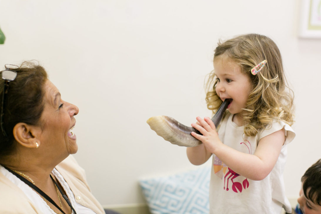 teacher showing a young girl how to blow a shofar or ram's horn