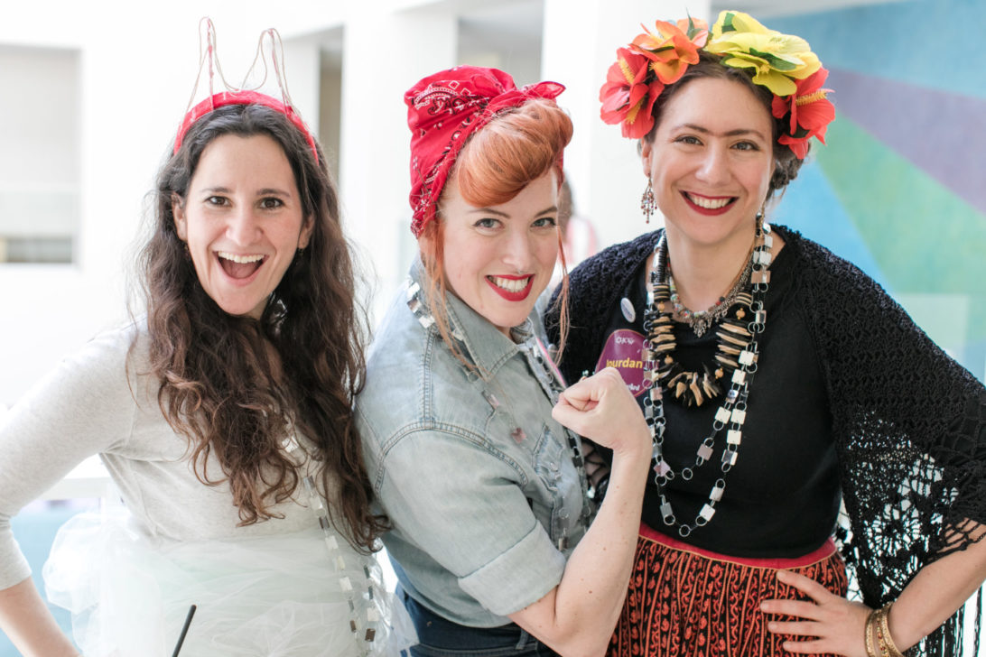 3 smiling women dressed up for the Jewish holiday of purim