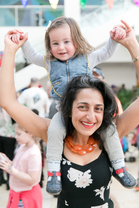 a woman carrying a small girl on her shoulders