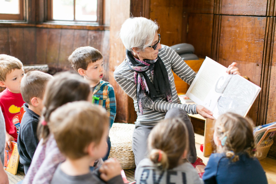 a woman with glasses and short white hair reading a book to preschool children who have gathered around