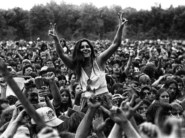 Woman throwing a double peace sign in a crowd.