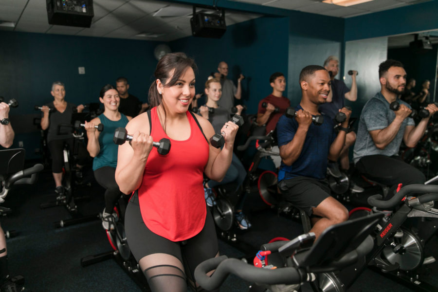 people working out on spin bikes and lifting weights