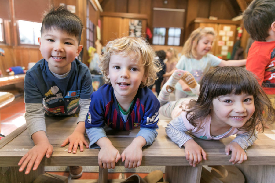 three preschool children leaning on a desk
